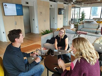 Three people sit around working together in an office