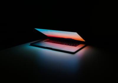 a laptop glows in a dark room, half open