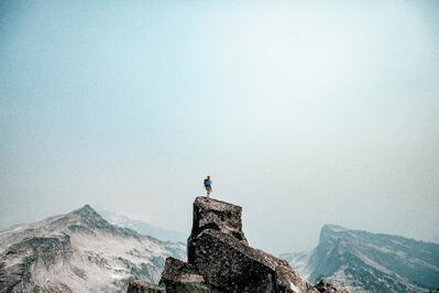 a climber at the top of a mountain looking out on the view