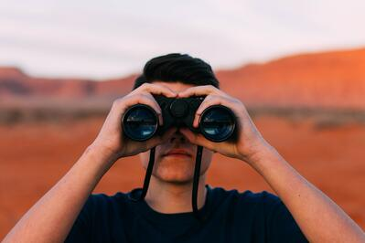 man takes a closer look at scenery with binoculars