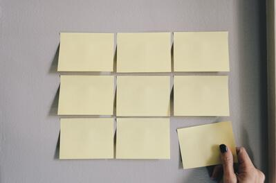 Hand adds a post-it to a wall