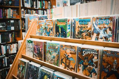 Superhero comics lined up on a shelf in a store