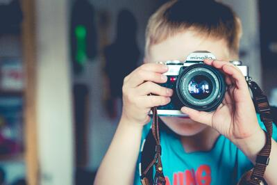 small boy takes photograph with camera