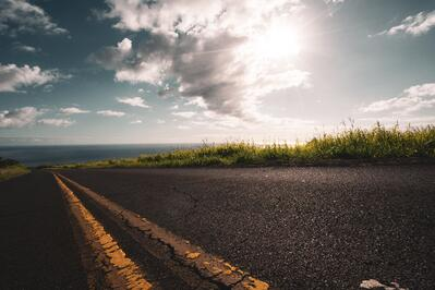 A road leading down to the sea with a sunny sky