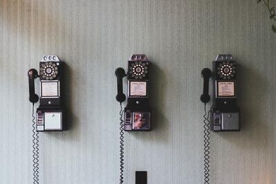 Old fashioned telephones lined up on a wall
