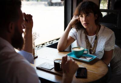 Woman listens to a man talking in cafe