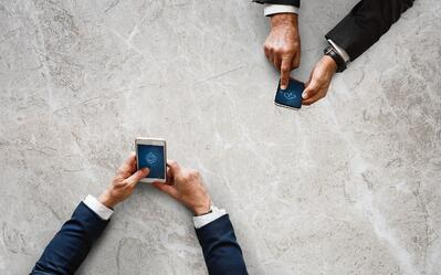 Two men transfer files to one another via their phones