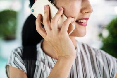Woman speaks on phone smiling