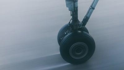A plane's wheel landing on landing strip