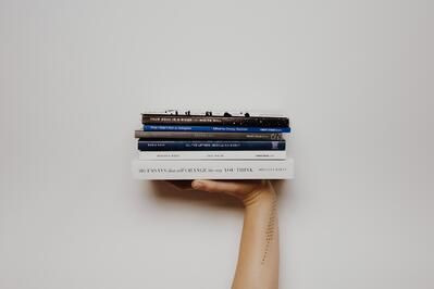 Stack of books being held by a hand